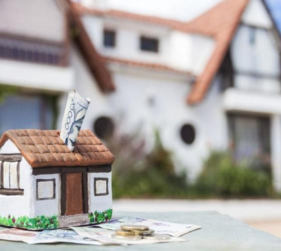 dinero en alcancia de casa con casa real de fondo