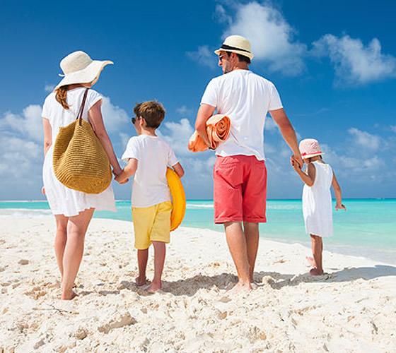 familia de vacaciones caminando por la playa
